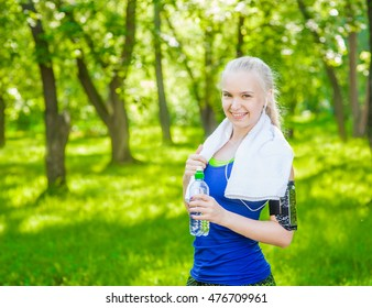 Attractive young blonde woman drinking water from plastic bottle after workout