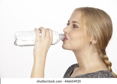 An attractive young blonde woman drinks mineral water out of a small plastic bottle. The studio shot is photographed over a white background.