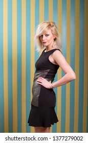 Attractive young blonde woman posing in front of striped yellow blue background while wearing open shoulder dark dress holding her hip