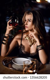 Attractive young blonde woman sitting in restaurant drinking glass of red wine on dark background