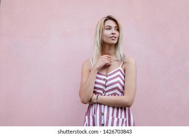 Attractive young blonde woman in a summer stylish striped sundress rests near a pink vintage wall in the city. Beautiful cute girl model outdoors. Fashion women clothes.