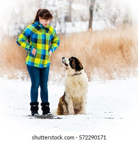 Attractive young boy and girl playing with a dog is on snow-covered field.