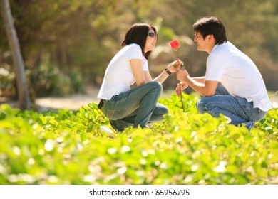 attractive young boy giving beautiful rose to his pretty girlfriend