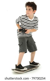 Attractive young boy on video game skateboard with joystick controller playing over white background.