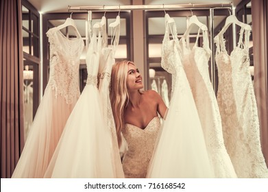 Attractive young bride is smiling while choosing wedding dress in modern wedding salon