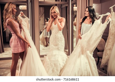 Attractive young bride is smiling while choosing wedding dress in modern wedding salon, girls are showing more dresses