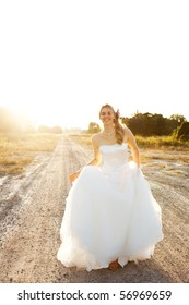 An attractive young bride wearing a white wedding dress is standing in the middle of a dirt road in a rural landscape. Vertical shot.