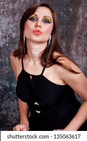 Attractive young brunette in a black dress with sexy lips.