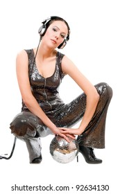 Attractive young brunette in headphones with a mirror ball. Isolated