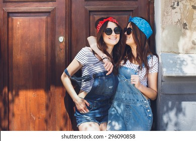Attractive young brunette twins girls, in stylish sunglasses, hugging and smiling. Having great time together. Wearing denim overalls bright bandanas, posing in front of old doors. Outdoors. Summer