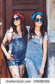 Attractive young brunette twins girls, in stylish sunglasses, hugging. Wearing denim overalls bright bandanas, posing in front of old doors. Outdoors. Summer day.