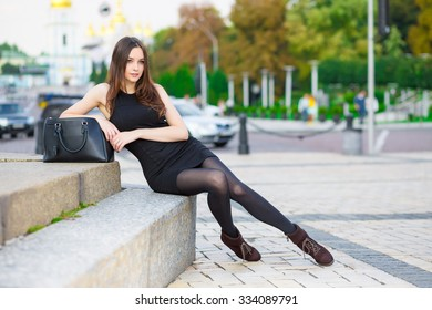 Attractive young brunette wearing black dress posing near the road