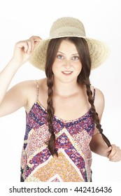 An attractive young brunette woman in a girly look with pigtails and a straw hat enjoys the summer isolated on white.