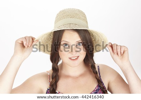 43da7abc An attractive young brunette woman in a girly look with pigtails and a  straw hat enjoys