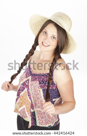 cf25ba74 An attractive young brunette woman in a girly look with pigtails and a  straw hat enjoys the summer isolated on white. - Image