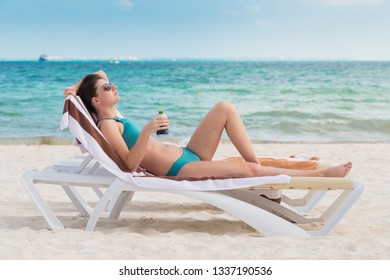 An attractive young brunette woman on a beach chair drinking a cold beer on a beach in Mexico