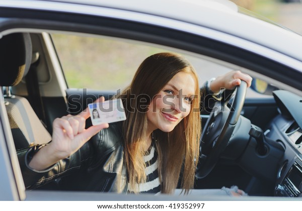 Attractive young brunette woman proudly showing her drivers license