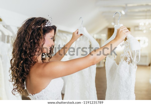 Attractive young brunette woman is smiling and enjoying while choosing wedding dress in modern wedding salon.