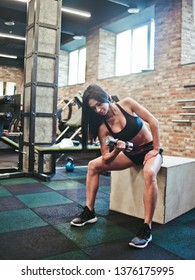 Attractive young brunette woman in sportswear doing exercise concentrated lifting on biceps dumbbells with one hand sitting on a wooden box in the gym