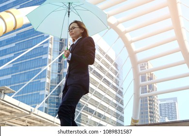 Attractive young business woman in black suit walking down in the stair under an blue umbrella, city as background. Business, bad weather and people concept