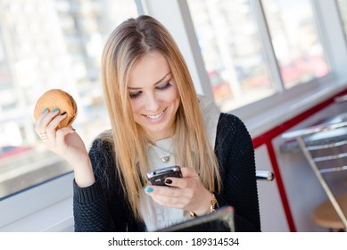 attractive young business woman eating a delicious burger in a cafe or restaurant having fun holding the mobile cell phone chatting and happy smiling closeup portrait