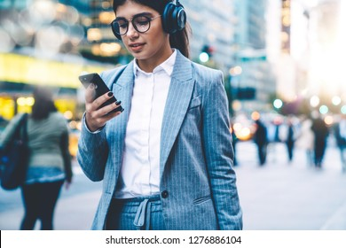 Attractive young business woman enjoying playlist in headphones while browsing LTE internet on smartphone. Female texting message on cellphone and listening to music. Media content in social networks