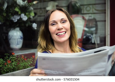 Attractive young business woman reading a newspaper somewhere in Europe near a cafe. A big laugh.
