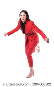 Attractive young business woman in red suit and high heels stumbling and falling. Full body isolated on white background.