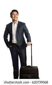 Attractive young businessman in a blue suit and white shirt, standing against a white background holding a bag getting ready for traveling.