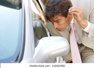 Attractive young businessman grooming using a car's reversing mirror to tidy his hair up, preparing for a business meeting.