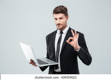 Attractive young businessman holding laptop and showing ok sign over white background