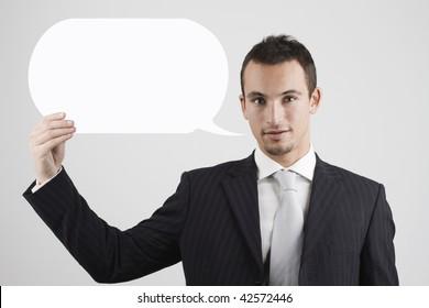 attractive young businessman holding a speech balloon .