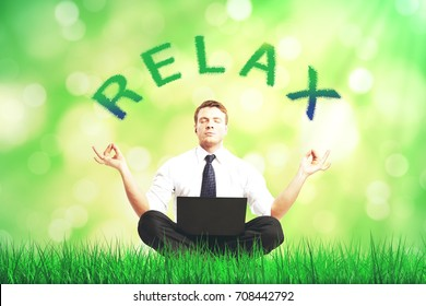 Attractive young businessman with laptop meditating on blurry green grass background. Relax concept