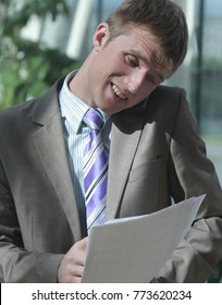 Attractive young businessman looking at document while talking