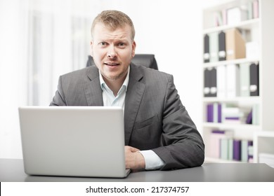 Attractive young businessman sitting at his desk in the office listening intently to the viewer leaning forward with an attentive expression on his face
