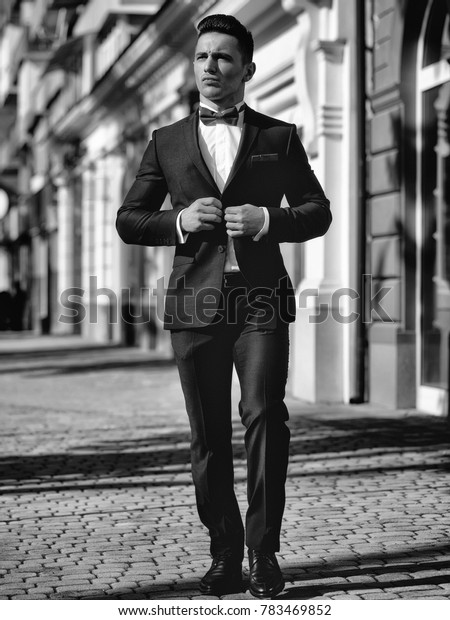 Attractive young businessman in urban background wearing suit and bow tie.
