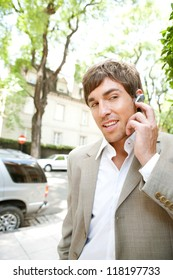 Attractive young businessman using a hands free ear piece device to make a phone call while in a classic city financial district, outdoors.