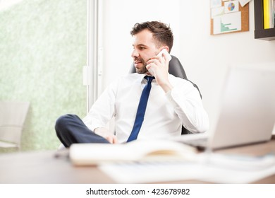 Attractive young businessman using his smartphone to make some calls to some clients