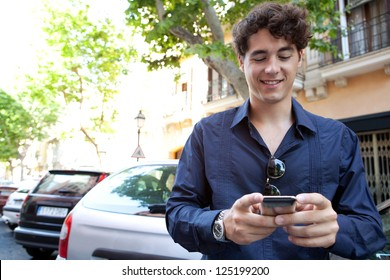 Attractive young businessman using a smart phone while standing in the city with cars parked behind him, smiling.