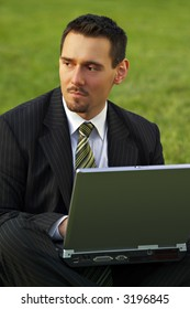 Attractive young businessman working with laptop in a park (green background), pondering.