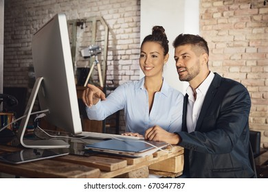 Attractive young businesspeople working together with computer.
