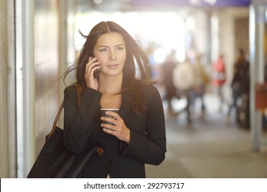 Attractive Young Businesswoman Calling on Mobile Phone, Walking Inside the Mall While Holding a Cup of Coffee.