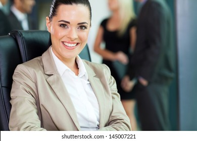 attractive young businesswoman closeup portrait with co-workers on background