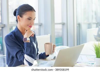 Attractive young businesswoman is enjoying hot tea