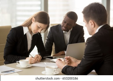 Attractive young businesswoman entitled to sign tripartite agreement putting signature on document at meeting with afroamerican and caucasian partners, accepted terms, agreed contract cost, ink deal