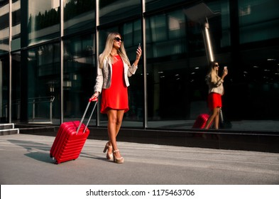 Attractive young businesswoman with her suitcase looking at smartphone, next to modern building / airport