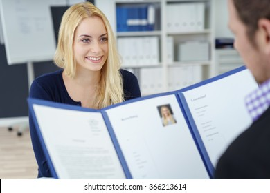Attractive young businesswoman in a job interview with a corporate personnel manager who is reading her CV in a blue folder, over the shoulder focus to the young applicant