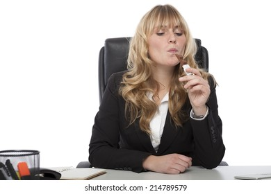 Attractive young businesswoman with long blond hair sitting at her desk enjoying a chocolate bar at work with a look of pleased anticipation