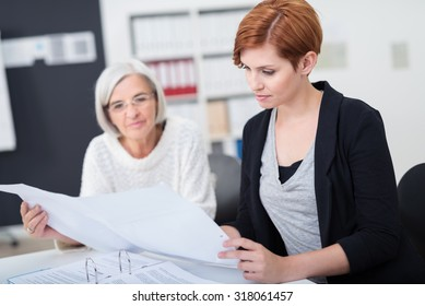 Attractive Young Businesswoman Reviewing Some Business Documents with her Senior Colleague Inside the Office.