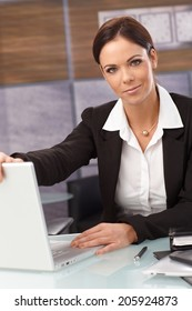 Attractive young businesswoman shutting down laptop, looking at camera, sitting at desk.